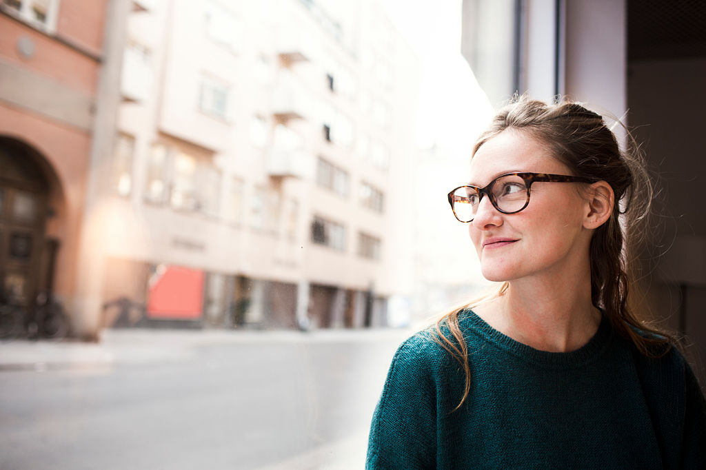 Smiling businesswoman wearing glasses while looking through office window